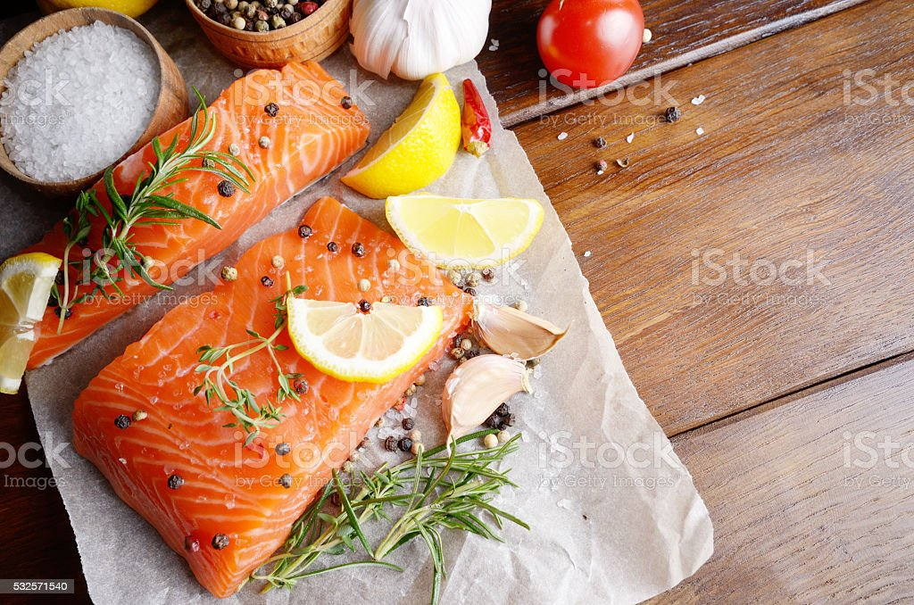 Raw salmon on baking paper stock photo