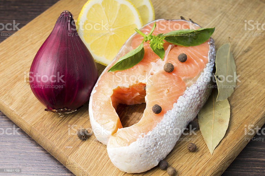 Raw Salmon Steak with Spices on wood Background royalty-free stock photo