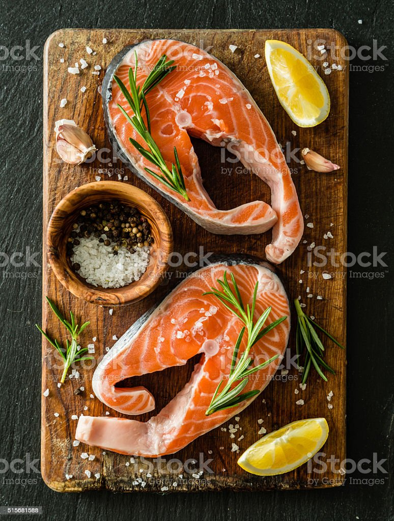 Raw salmon steaks on rustic background stock photo