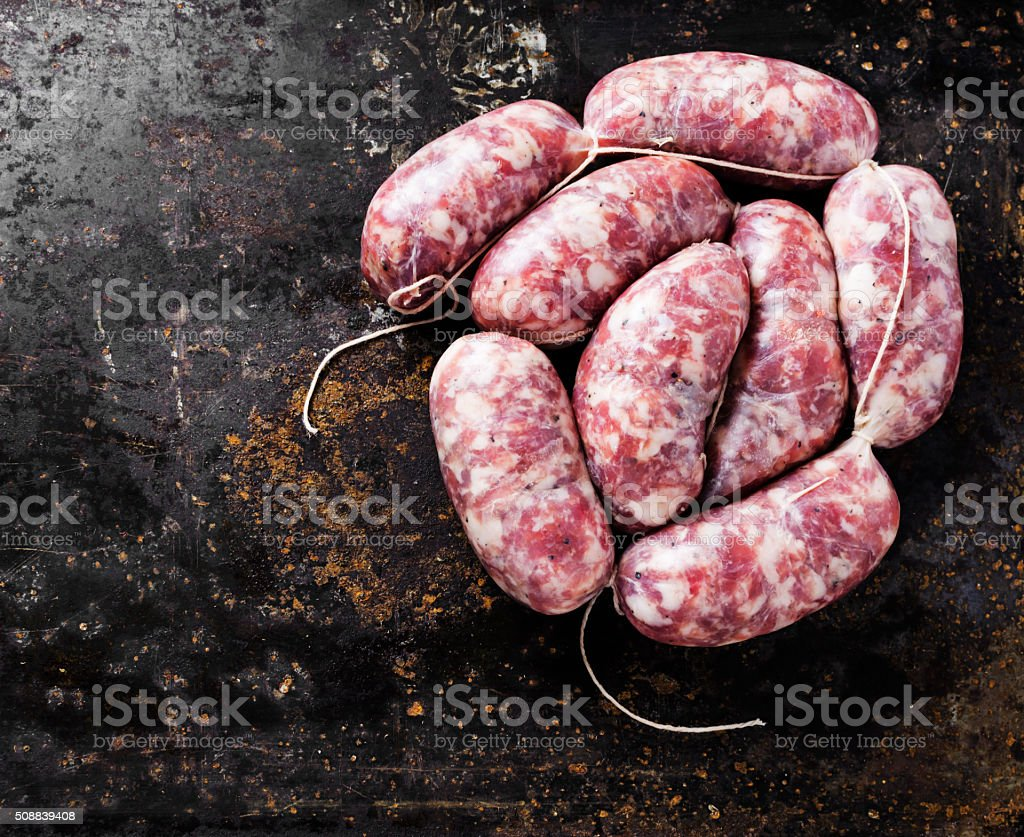Raw sausage with spices on a dark background stock photo