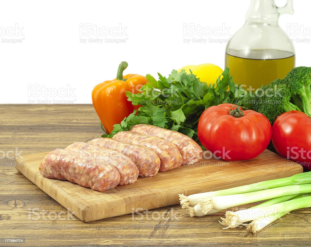 Raw sausages and fresh vegetables on a cutting board royalty-free stock photo