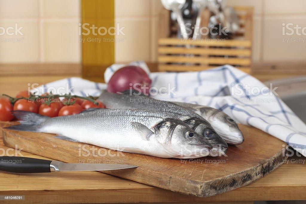 Raw sea bass on a wooden cutting board stock photo
