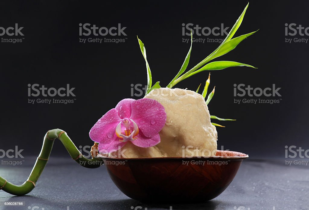 Raw shea butter in wooden bowl with orchid and bamboo stock photo