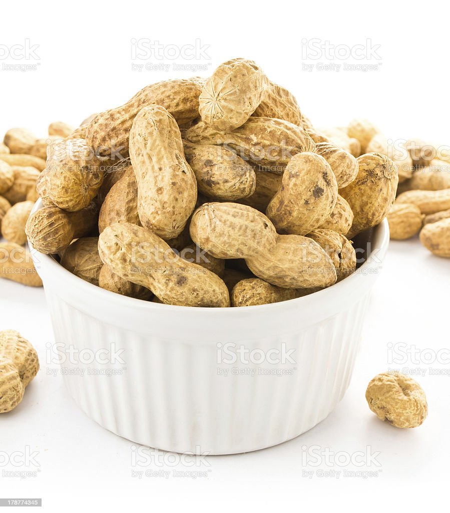 Raw shelled great peanuts in a bowl on white background royalty-free stock photo