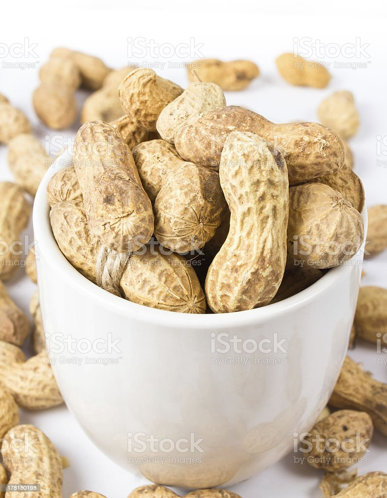 Raw shelled great peanuts in a cup on white background, royalty-free stock photo