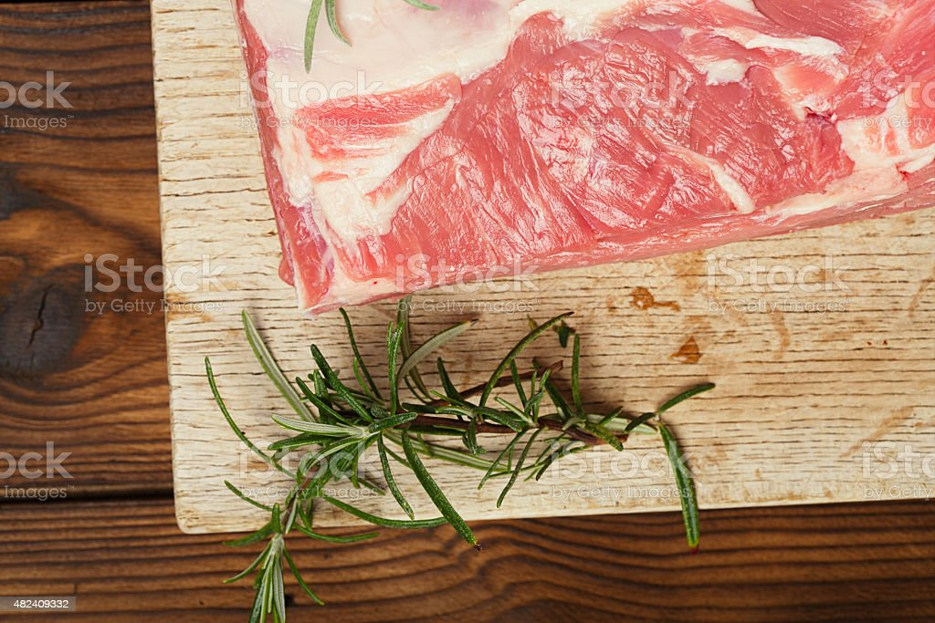 raw shoulder lamb on wooden board and table stock photo