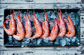 Raw shrimp tray with ice on blue wooden table