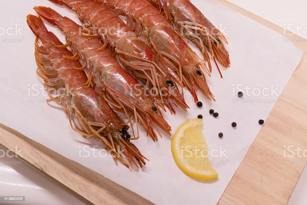 Raw shrimps ready for cooking with lemon, pepper stock photo