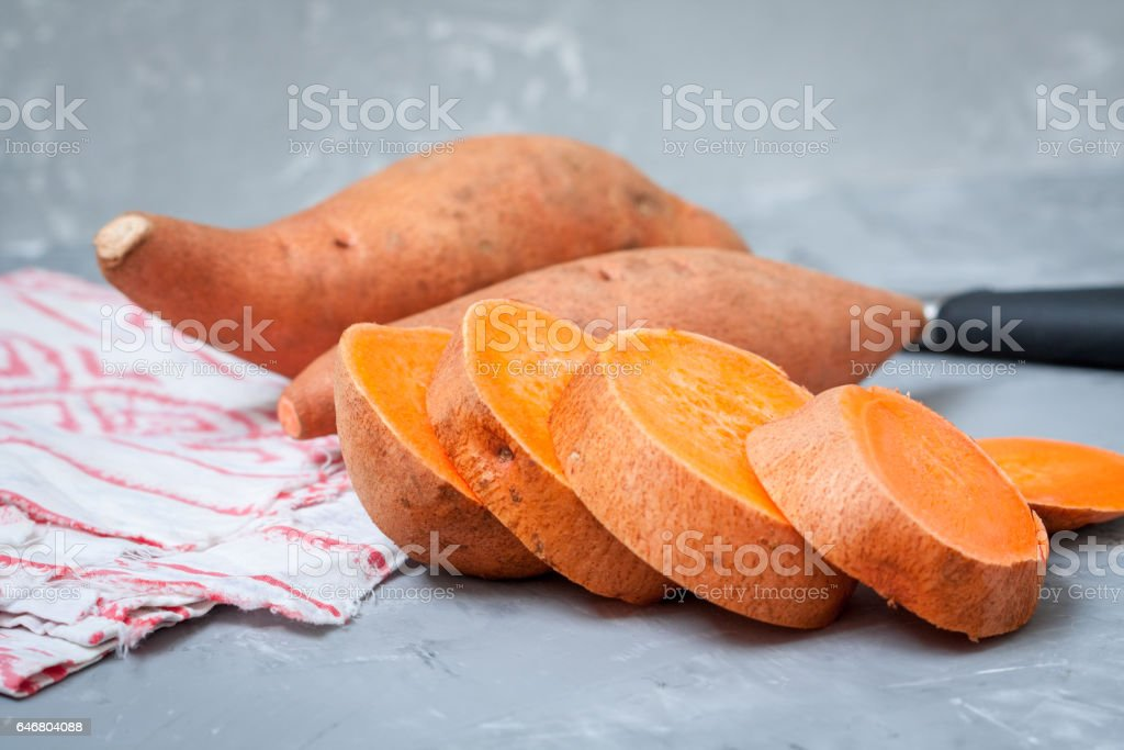 Raw sliced and whole sweet potatoes stock photo