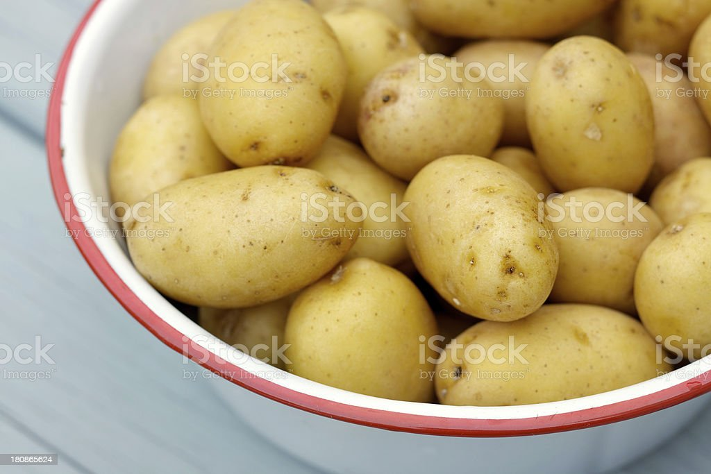 Raw small potatoes in metal bowl on wood table royalty-free stock photo