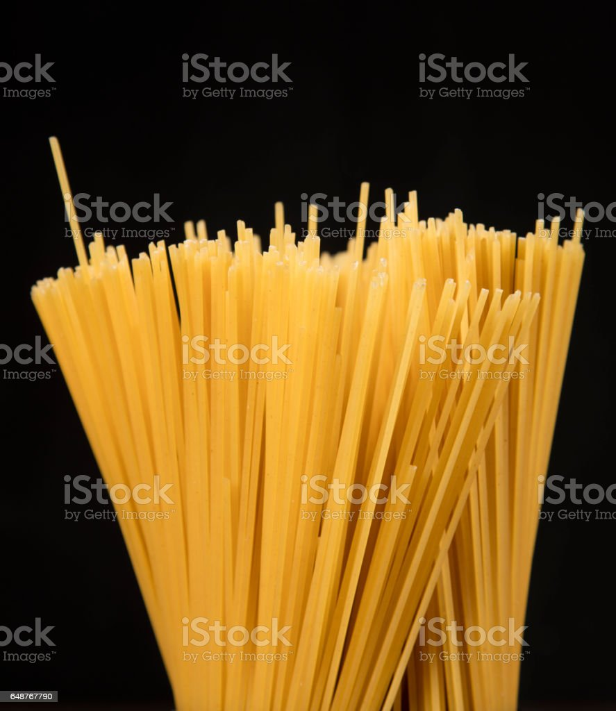 raw spaghetti pasta scattered on old wooden table, close-up view from above stock photo