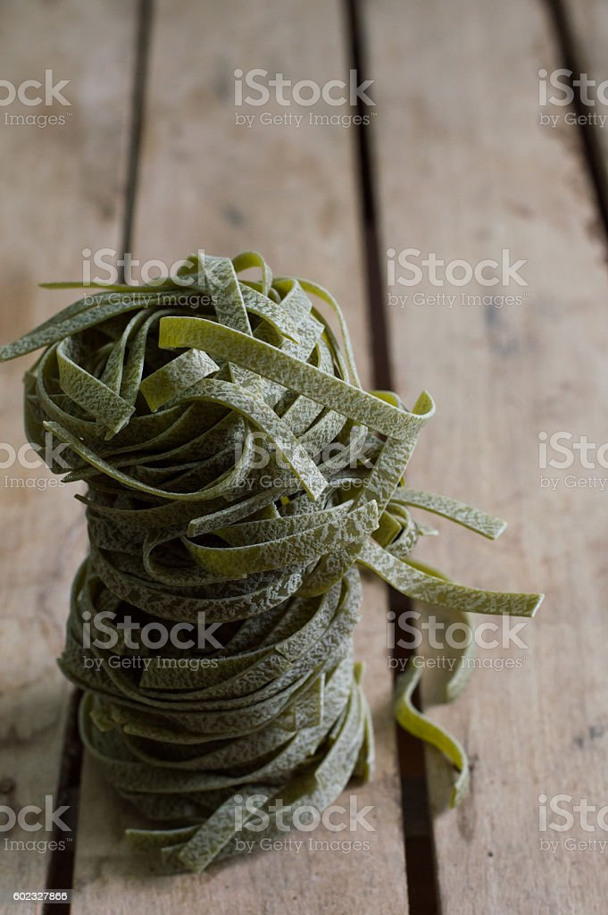 Raw spinach pasta on a wooden table stock photo