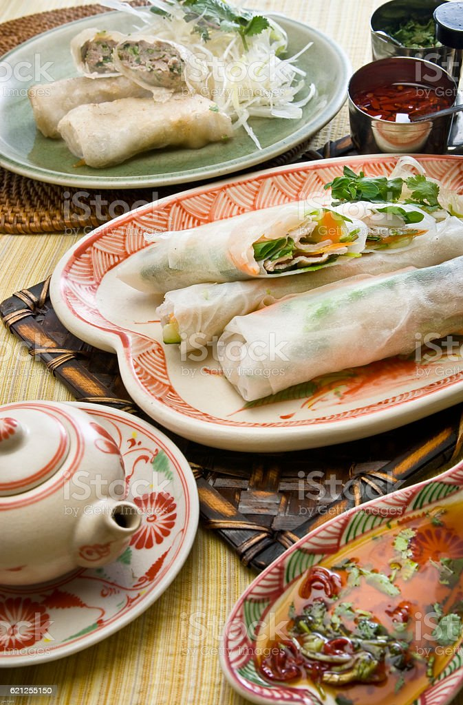 Raw spring rolls and fried spring rolls stock photo