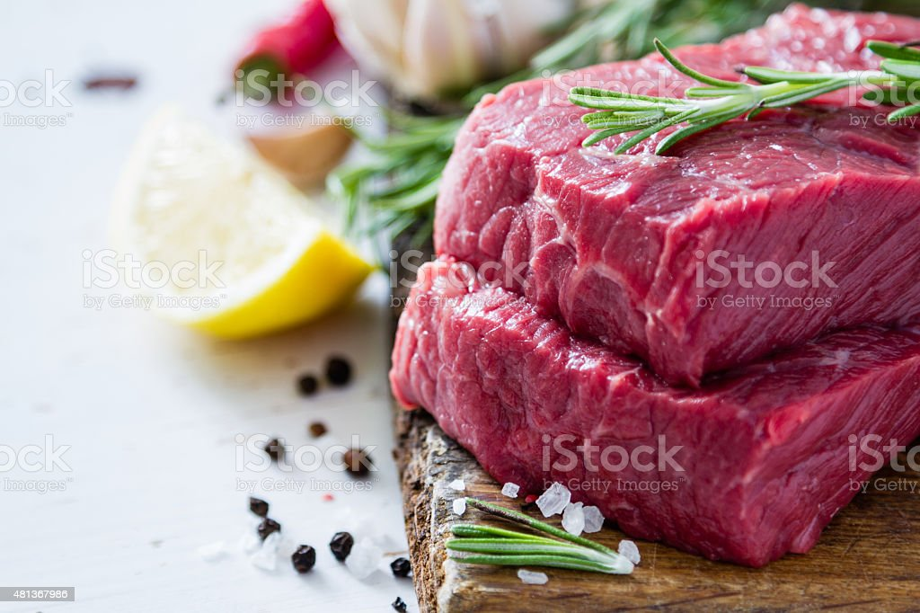 Raw steak and ingredients on wood board stock photo