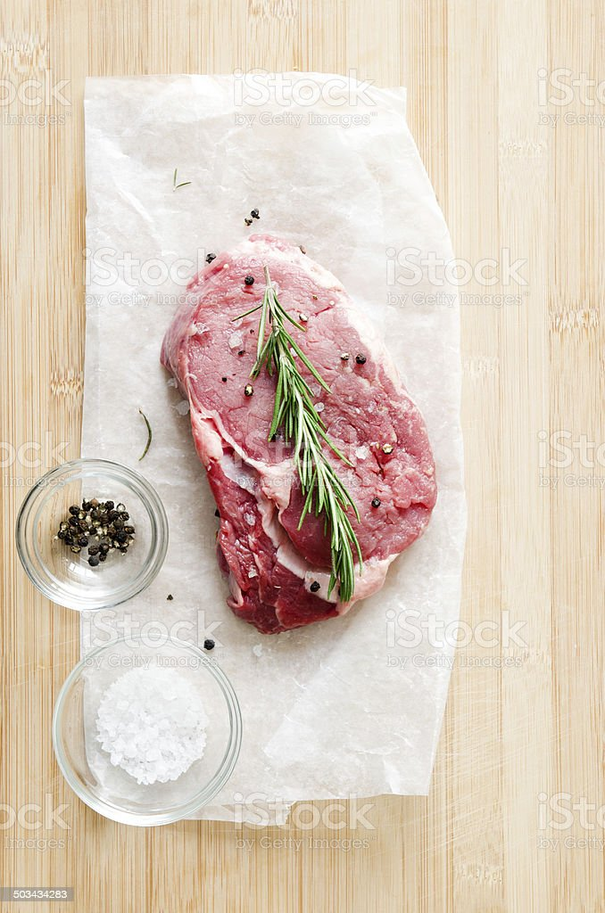 Raw steak on wooden surface with salt and pepper stock photo