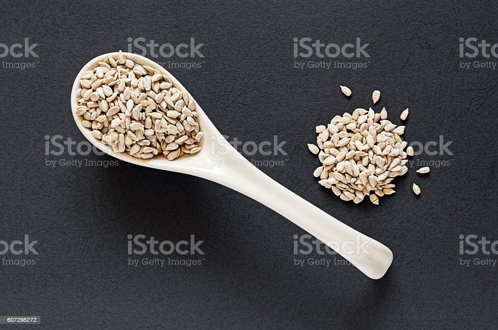 Raw Sunflower Seeds in a Porcelain Spoon stock photo