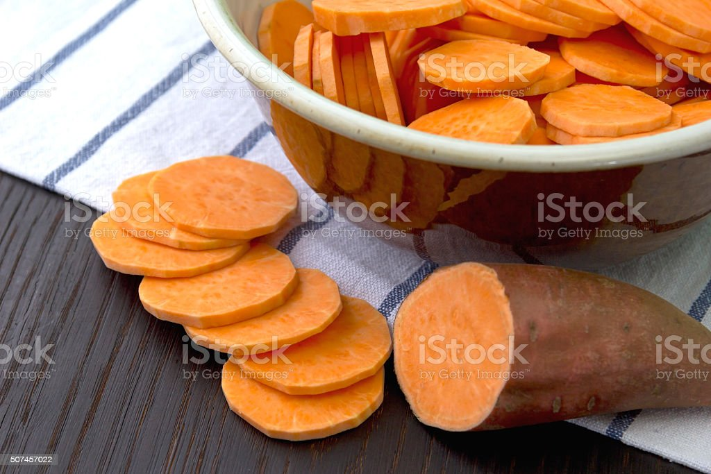 Raw sweet potato with at the wooden table stock photo