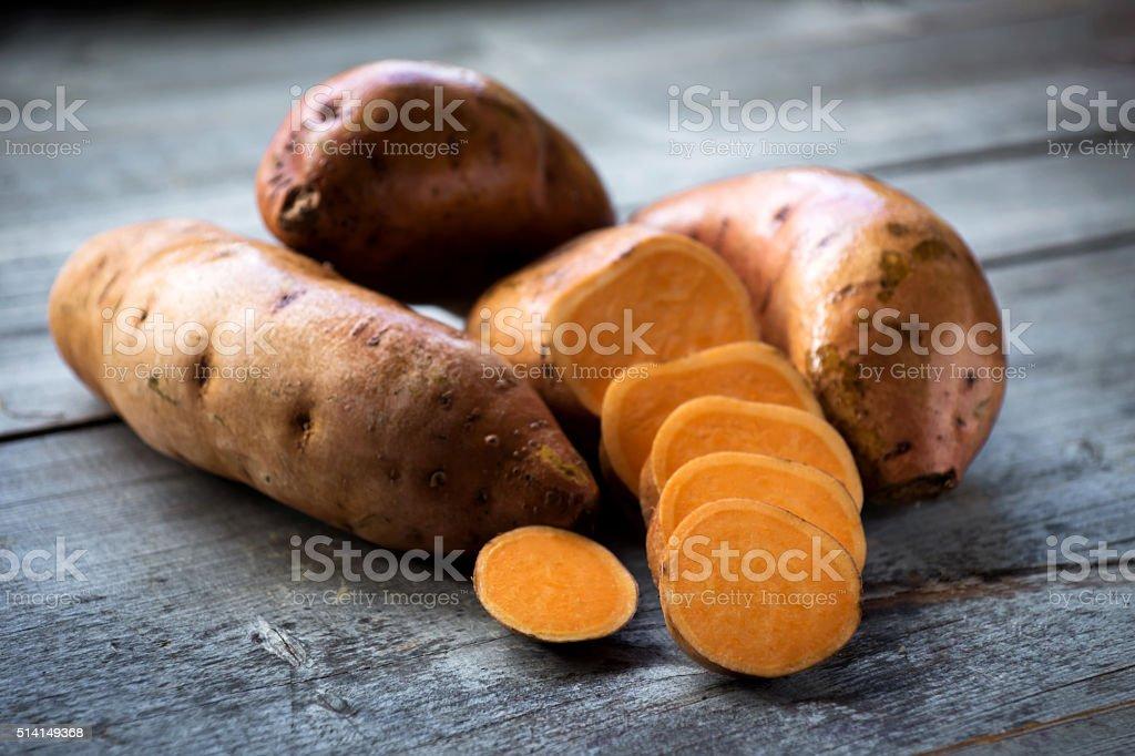 Raw sweet potatoes on wooden background closeup stock photo