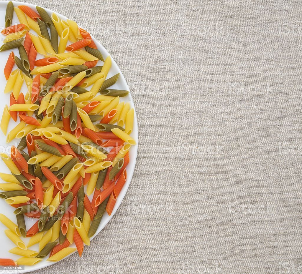 Raw three-colored Italian pasta on a round white plate stock photo