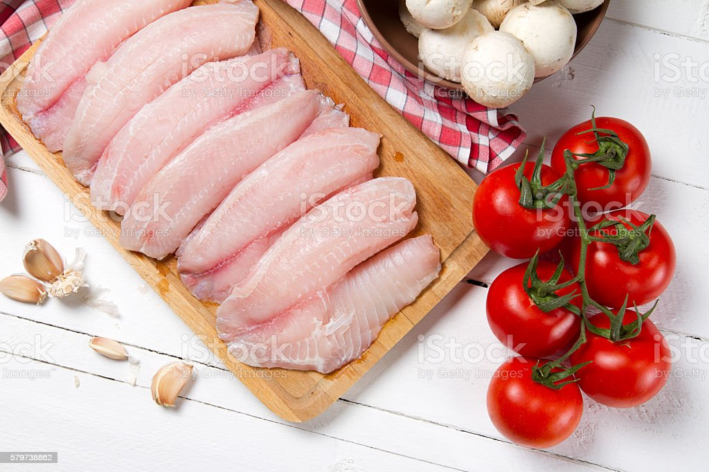 Raw tilapia fillet on a wooden board stock photo