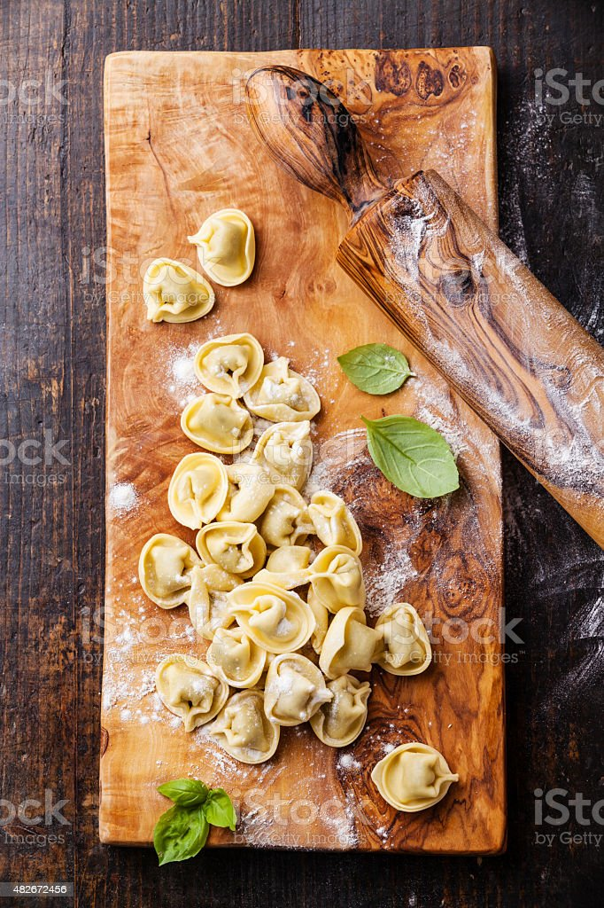 Raw Tortellini and basil leaves stock photo