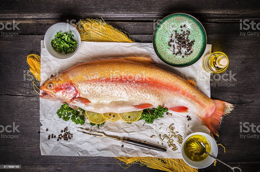raw trout on dark wooden table with herb and lemon stock photo