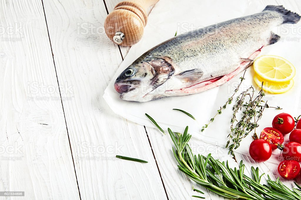 Raw trout, rosemary, tomatoes, lemon, thyme stock photo