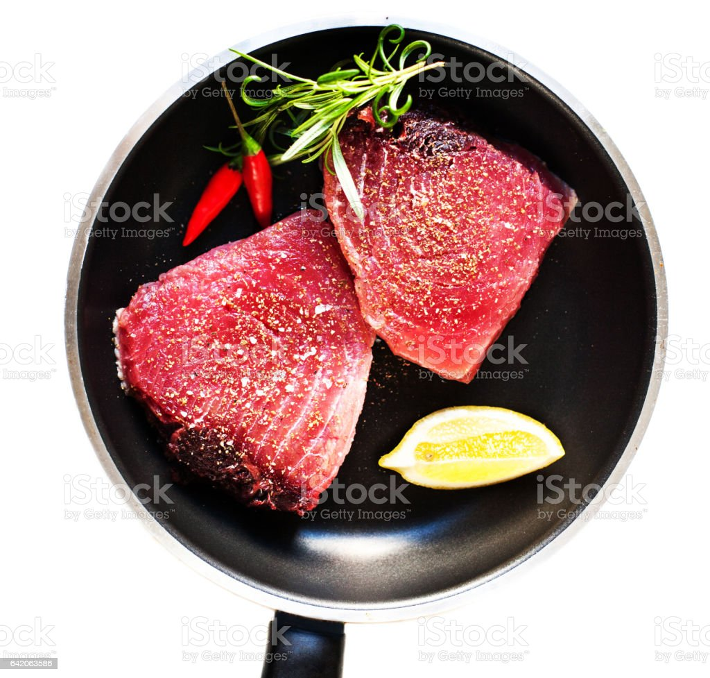 Raw tuna on a frying pan close up isolated on white background stock photo
