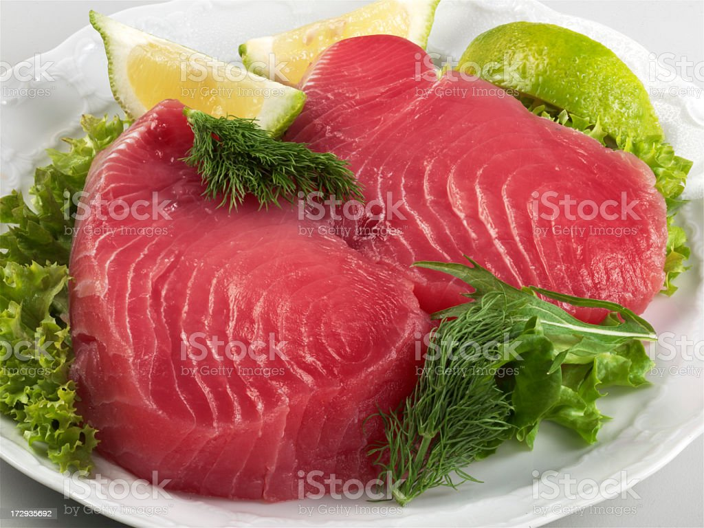 Raw tuna steaks on a plate with salad  stock photo
