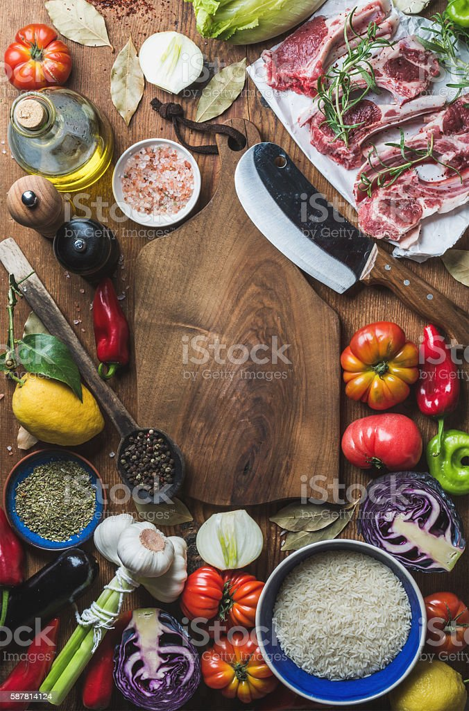Raw uncooked lamb meat chops, rice, oil, spices and vegetables stock photo