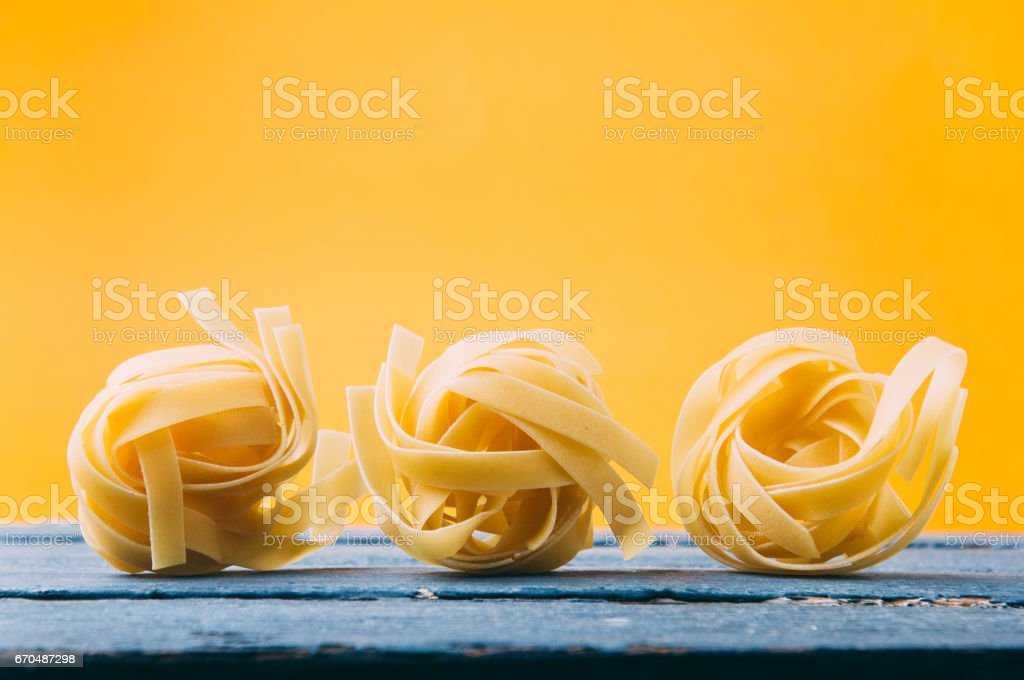 Raw uncooked pasta over yellow background stock photo