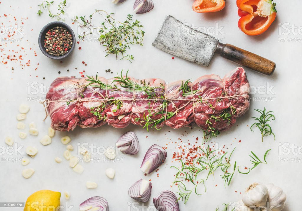 Raw uncooked roast beef meat with herbs, vegetables, spices stock photo