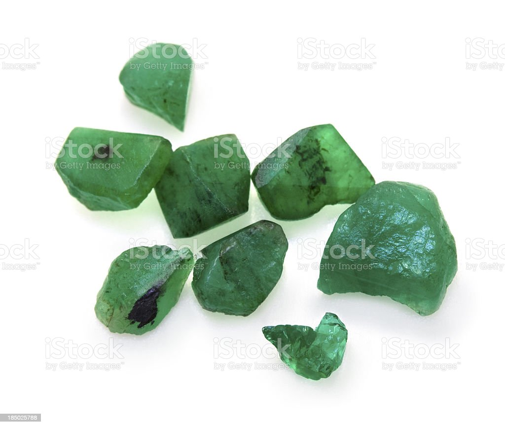 Raw uncut green emerald gemstones isolated on white background. stock photo