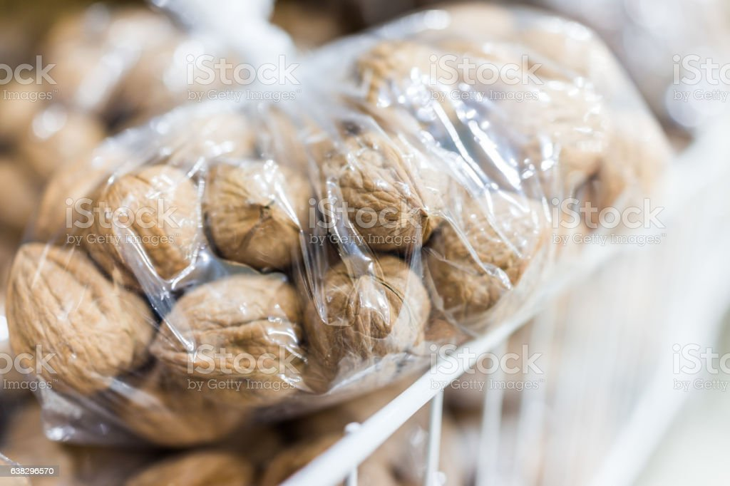 Raw unshelled walnuts in plastic bags for sale stock photo