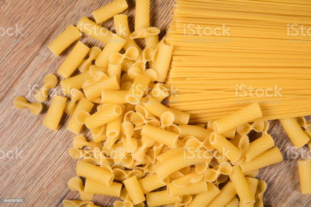 raw various pasta scattered on old wooden table, close-up view from above stock photo