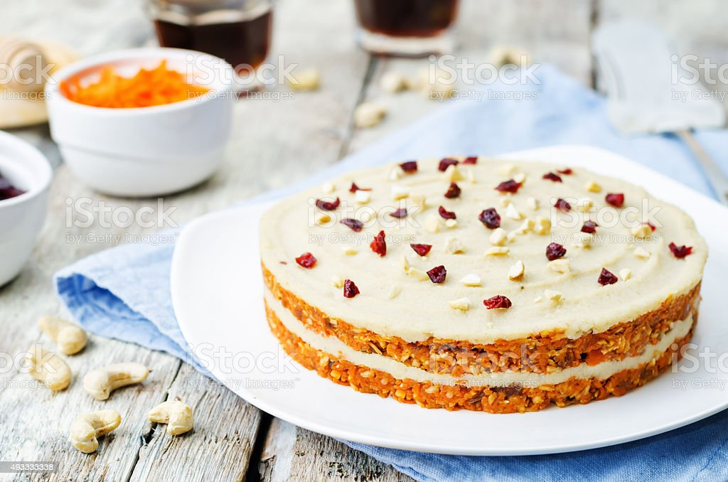 raw vegan carrot cake with cashew cream and dried cranberries stock photo
