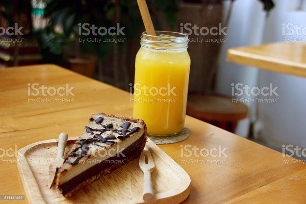 raw vegan chocolate cheesecake and orange juice stock photo
