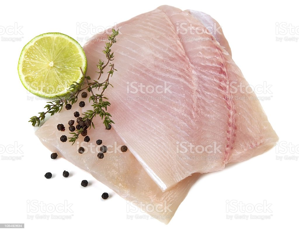 Raw white fish fillets with lime slice royalty-free stock photo