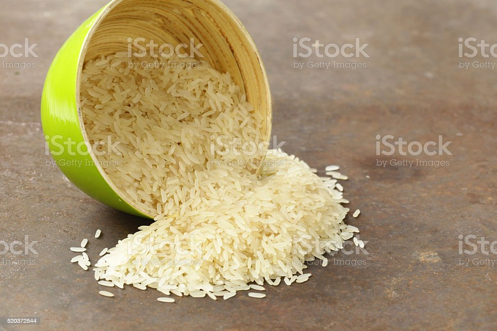 raw white rice in a bamboo bowl stock photo