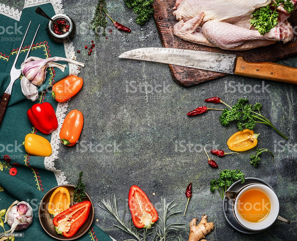 Raw whole chicken with ingredients for cooking on rustic background stock photo