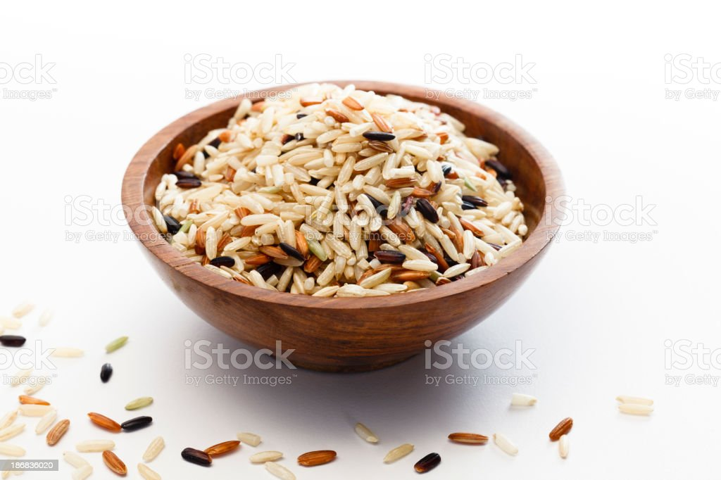 Raw wild brown rice blend on a wooden bowl stock photo