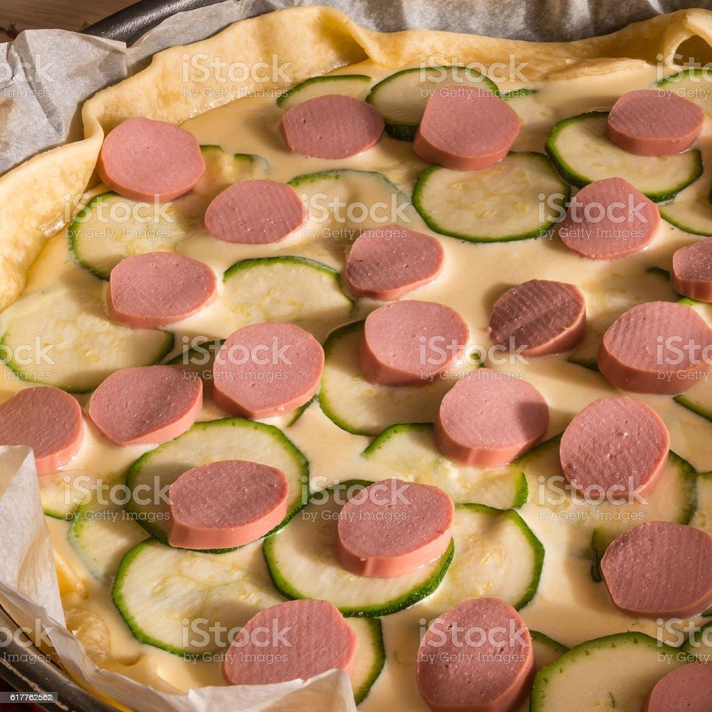 raw wurstel and zucchini savoury pie, puff stock photo