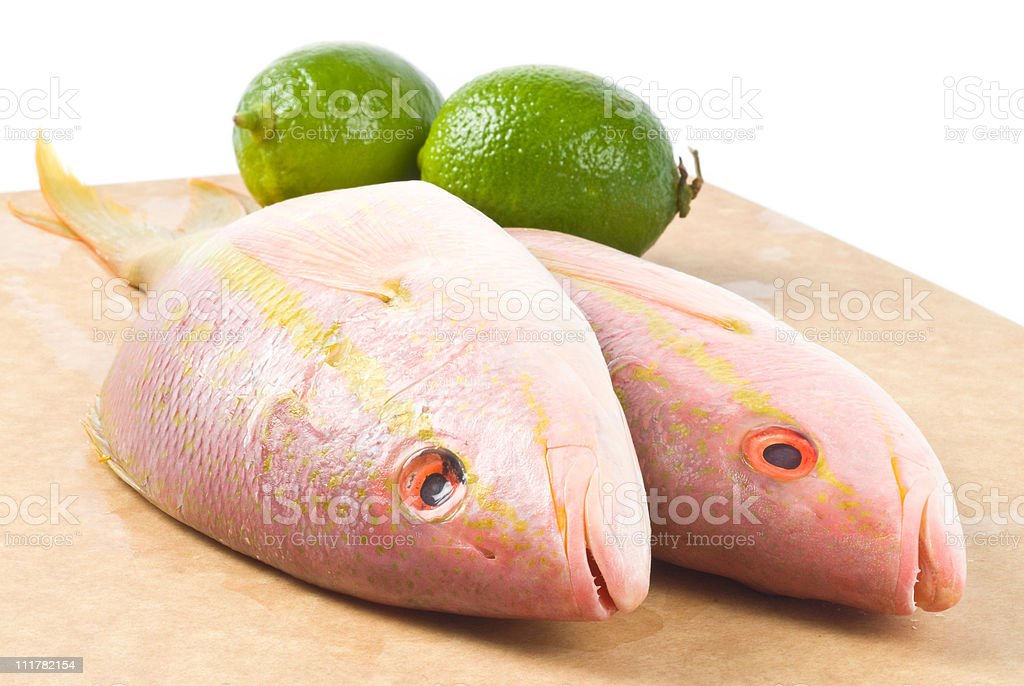 Raw Yellow Tail Snappers and Fresh Limes stock photo