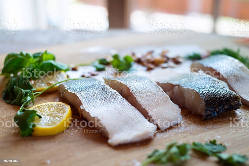Raw zander fish fillets with lemon slices and herbs. stock photo
