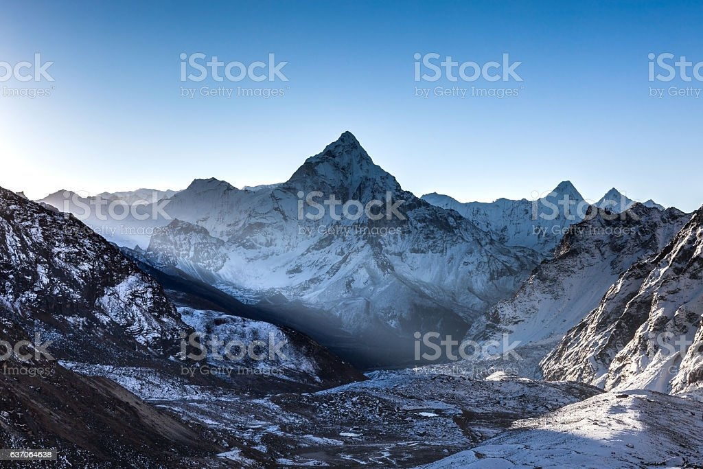 Ray of light beaming through mountains in front of stock photo