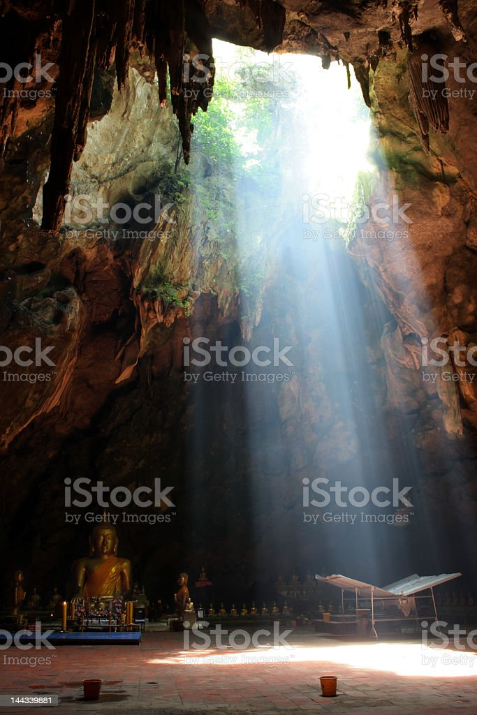 Ray of sunlight breaking into Tham Khao Luang Cave stock photo