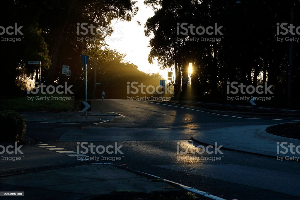 Rays from Sunrise Falling Across a Darkened Country Road stock photo
