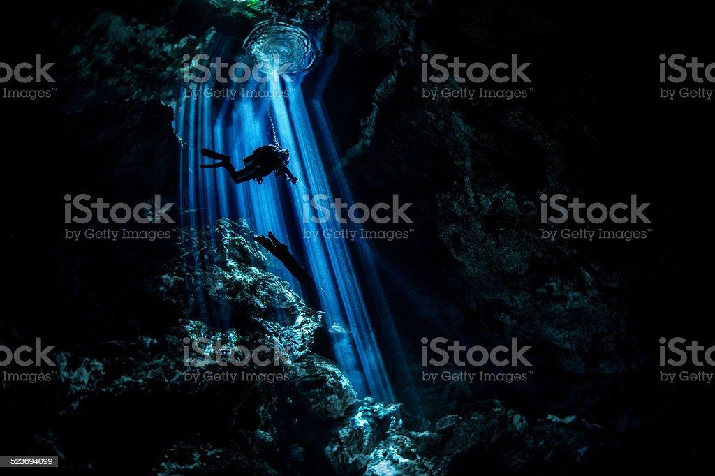 Rays of light in dark underwater cave stock photo