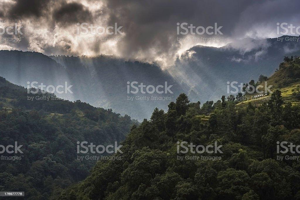Rays of light shining onto mountain farm green jungle Himalayas stock photo