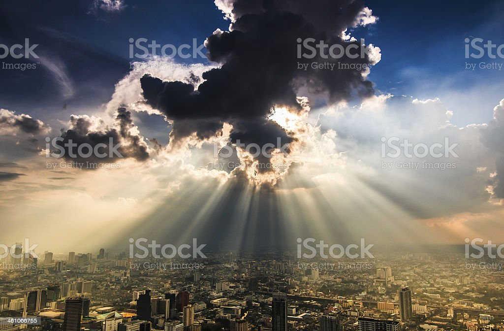 Rays of light shining through dark clouds city Bangkok, Thailand stock photo